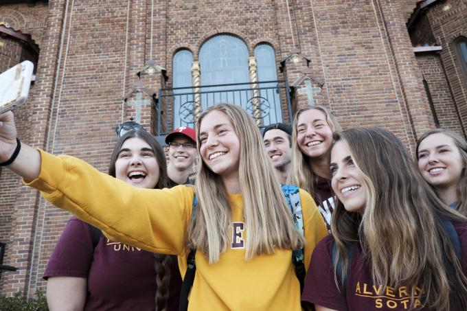 Students posing for a selfie in front of Francis Hall