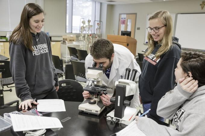 Biology professor demonstrating to students how to use a microscope.