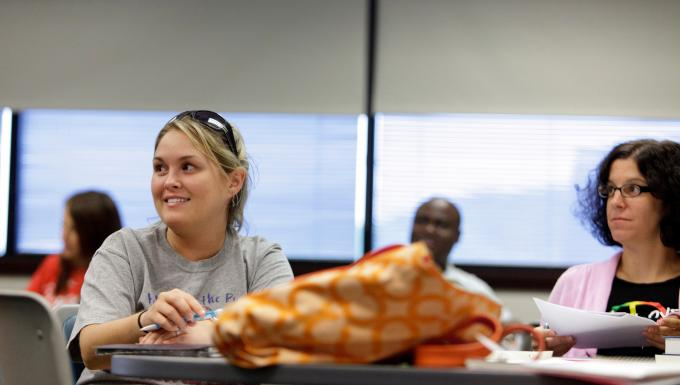 A female student smiles in an adult education class.