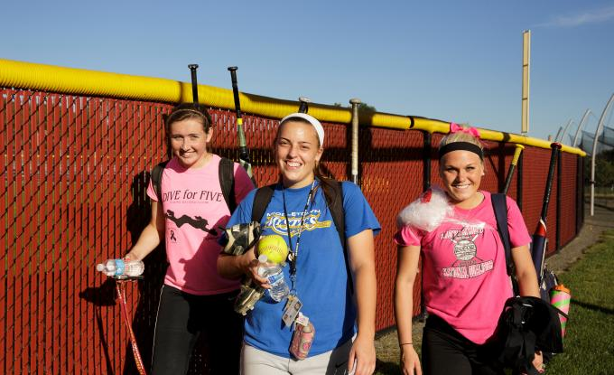 Softball players leave field