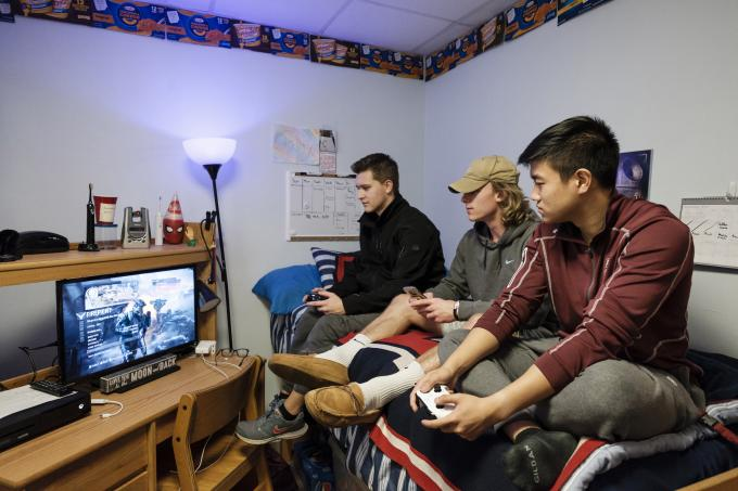Students playing video games in dorm room