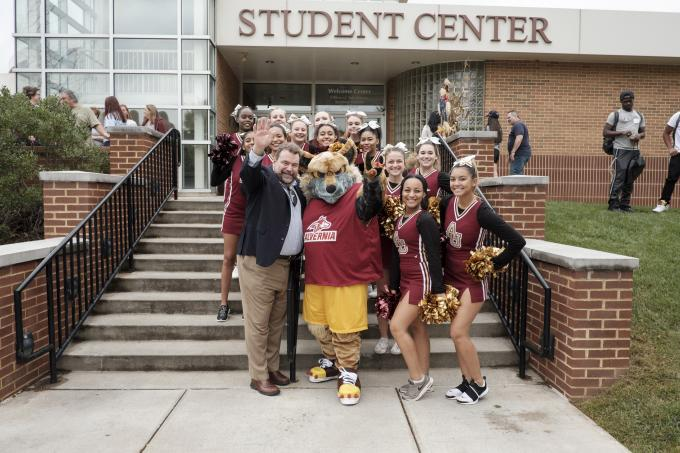 Dr. Flynn and cheerleaders at homecoming