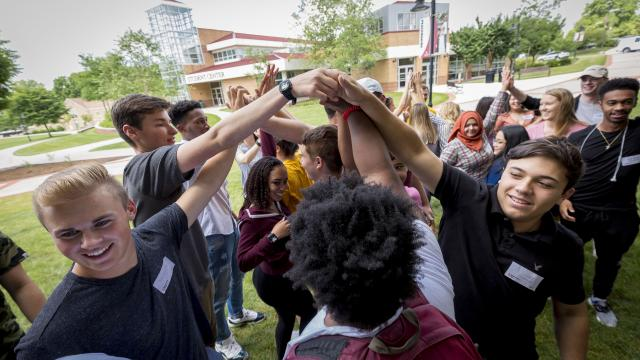 Students join hands in the quad